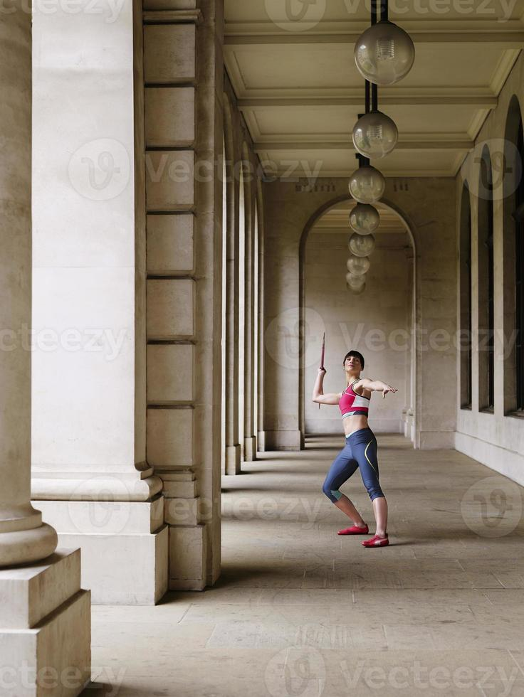 Sportlerin, die Speer in Portikus wirft foto