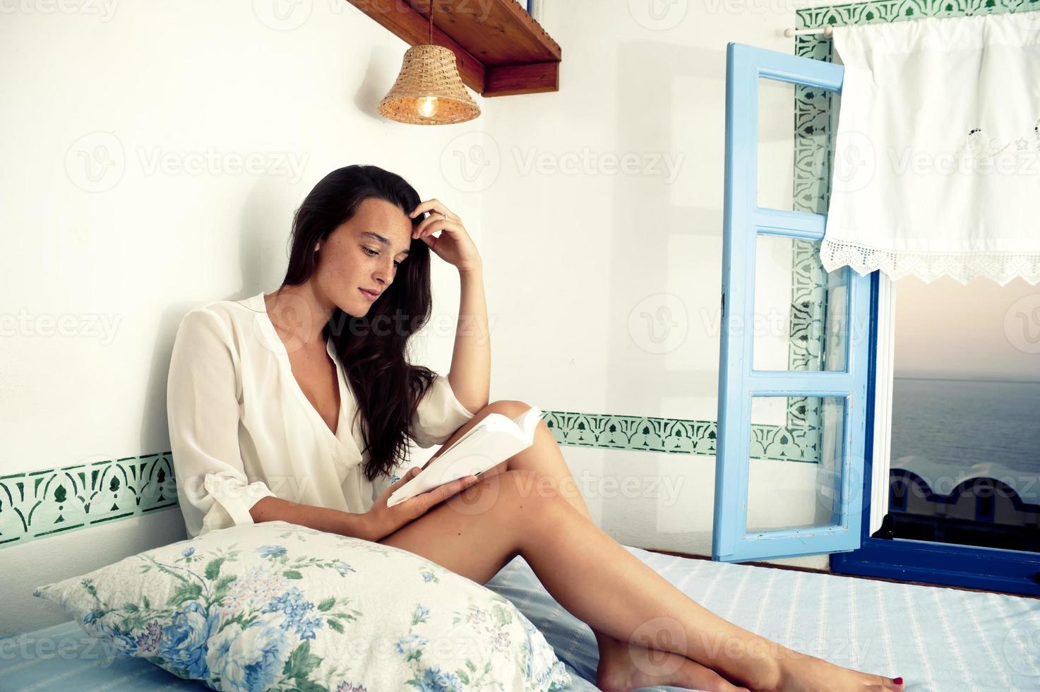 junges weibliches Lesebuch auf Bett foto