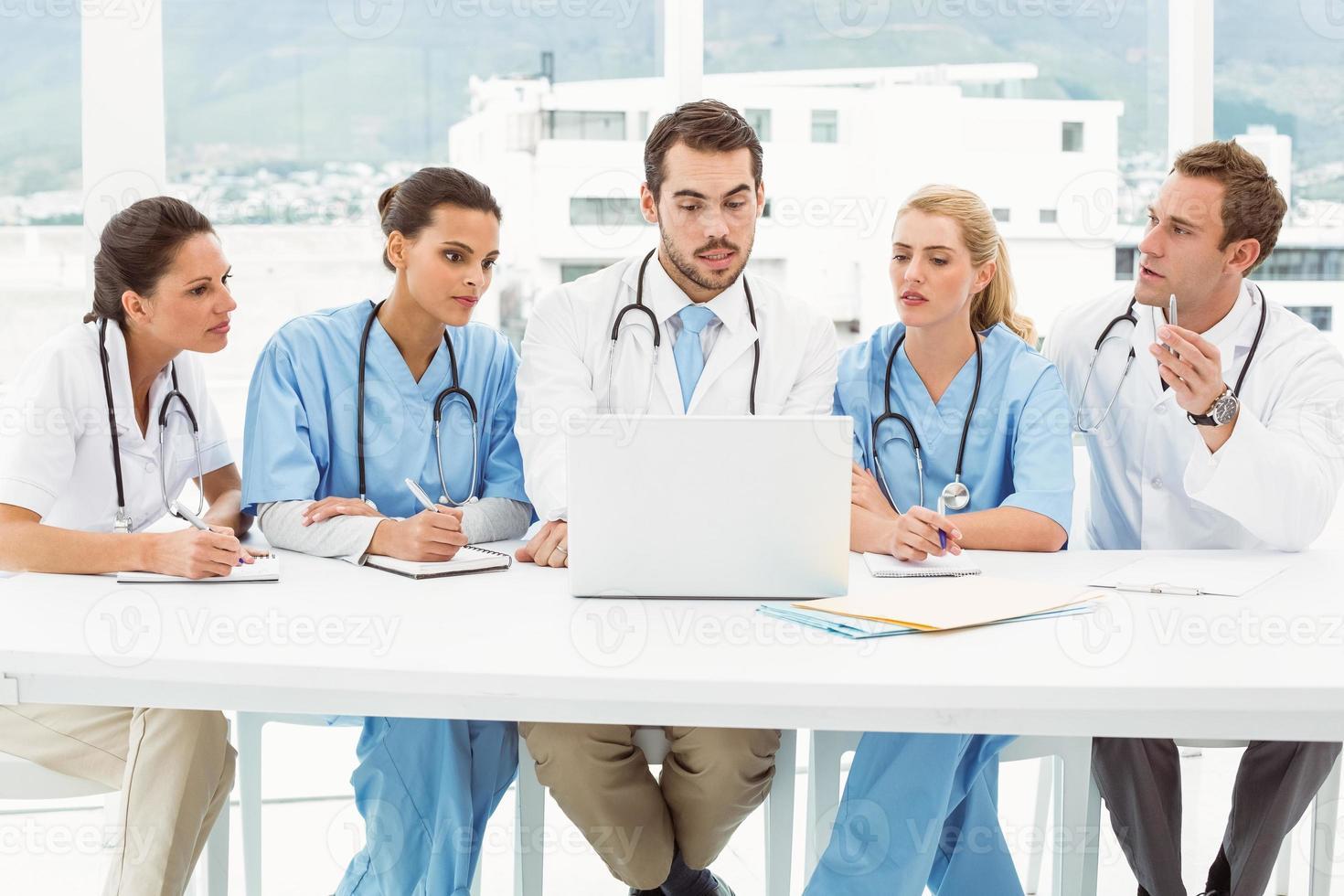 männliche und weibliche Ärzte mit Laptop foto