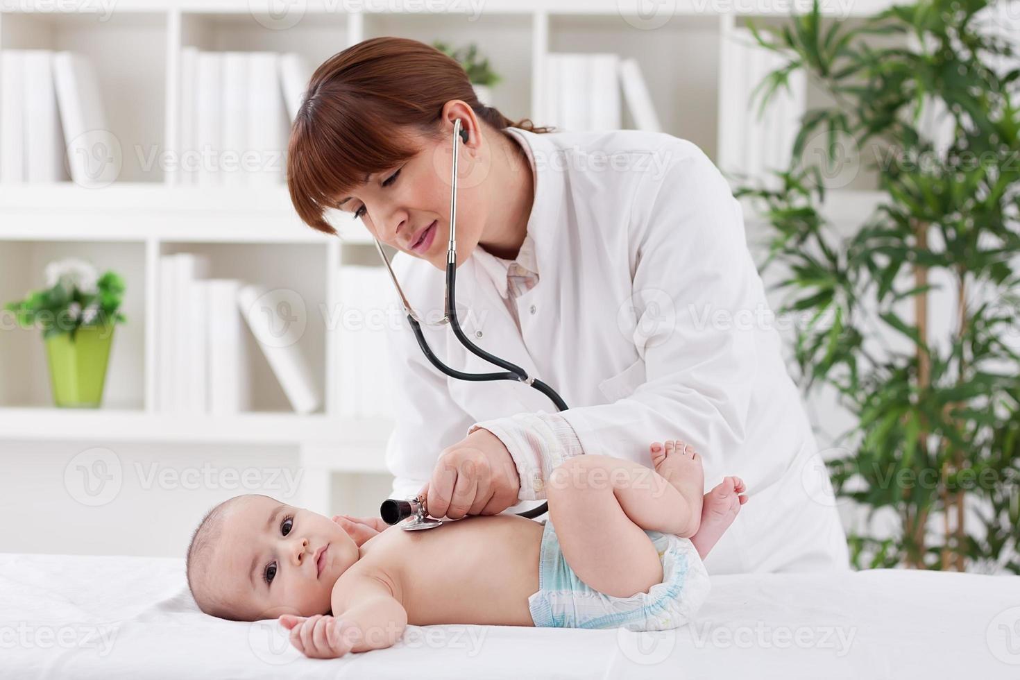 junge Ärztin, die einen Babypatienten untersucht foto