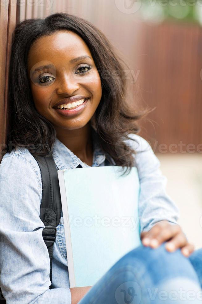 weiblicher afrikanischer College-Student, der draußen sitzt foto
