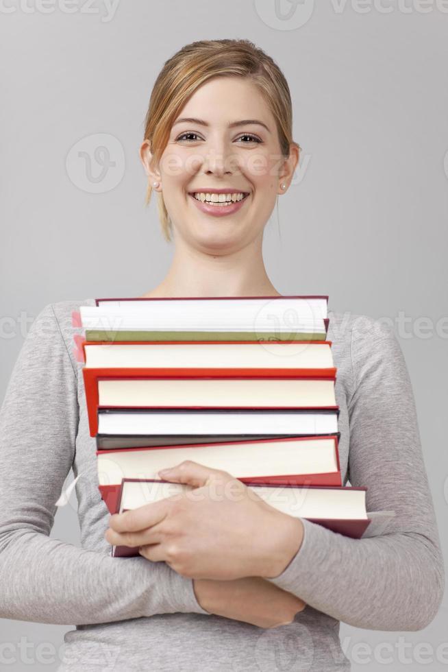 Studentin mit Stapel Bücher foto