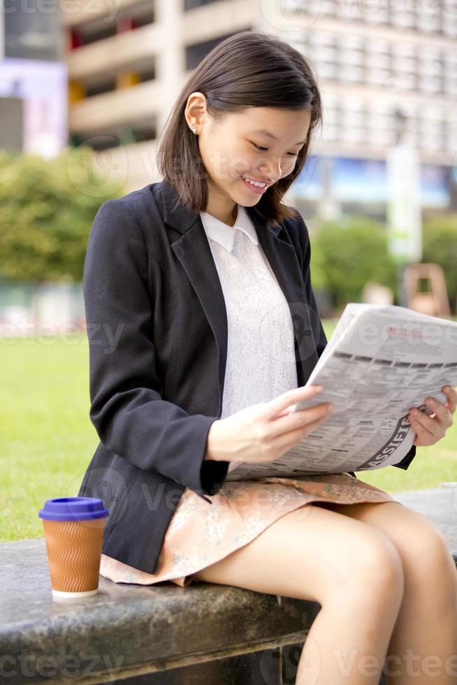 junge asiatische Geschäftsführerin, die Zeitung liest foto