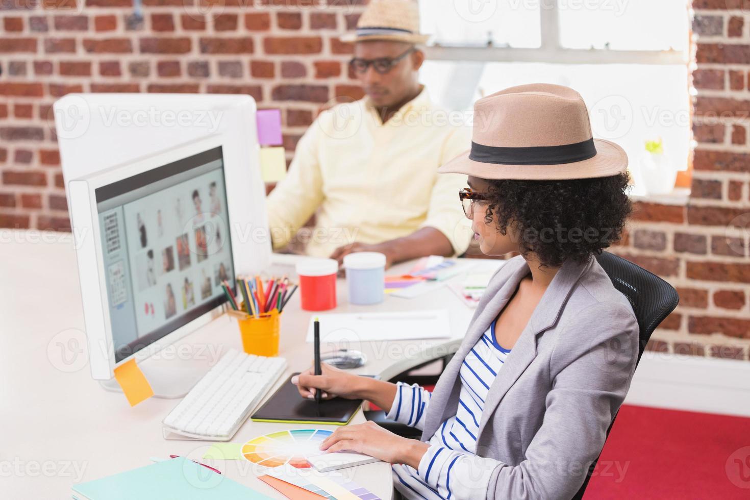 weiblicher Bildbearbeiter mit Digitalisierer im Büro foto
