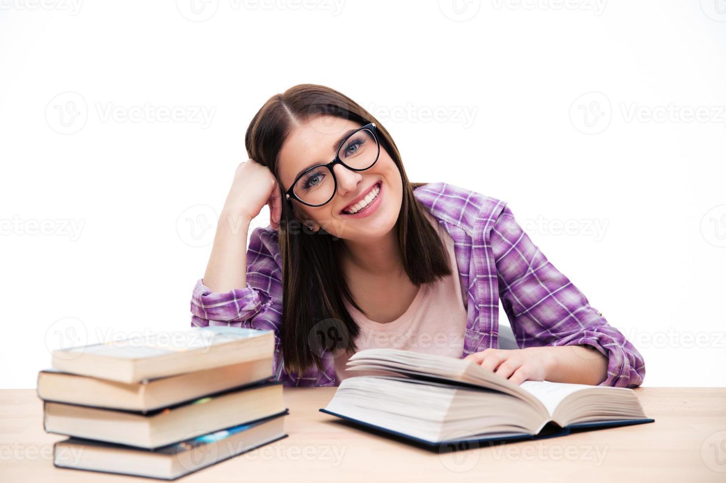 glückliche Studentin, die am Tisch sitzt foto