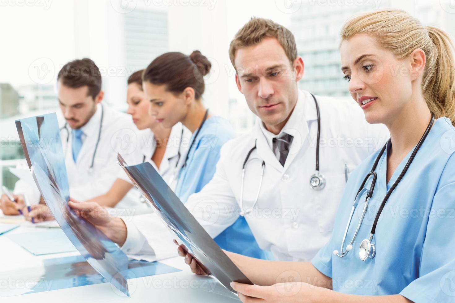 männliche und weibliche Ärzte, die Röntgen untersuchen foto