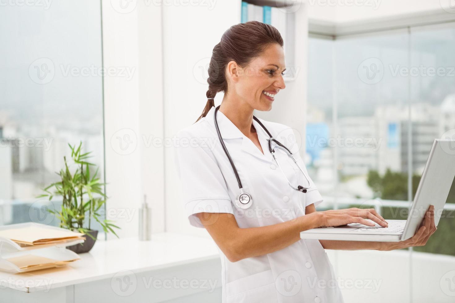Ärztin mit Laptop in der Arztpraxis foto