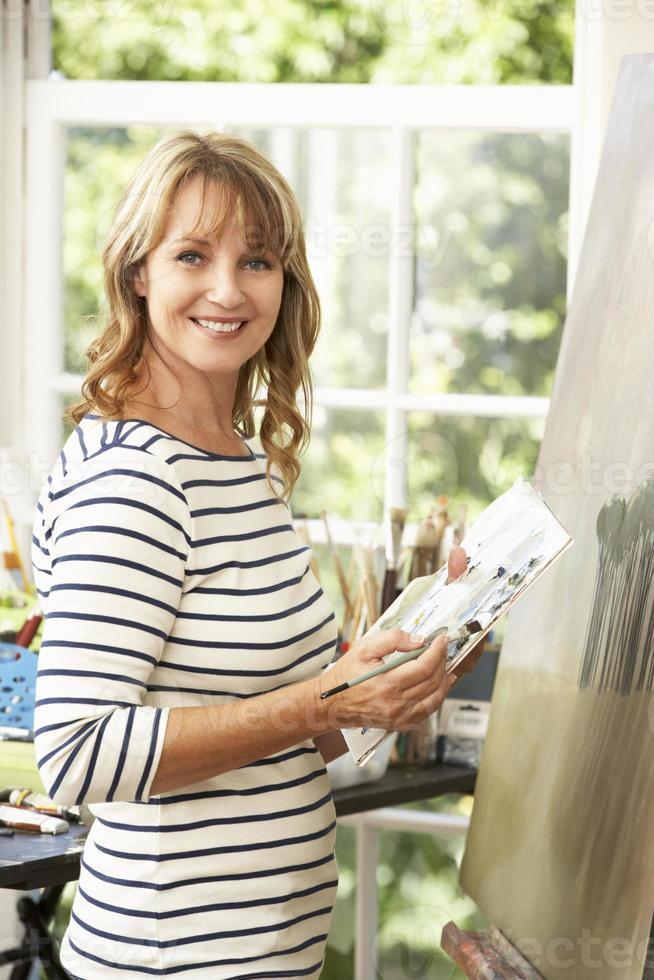 Künstlerin, die an der Malerei im Studio arbeitet foto