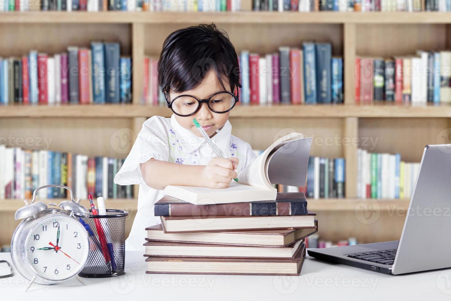 schöne Studentin, die in der Bibliothek schreibt foto