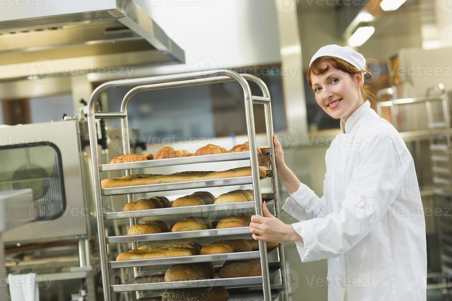 hübsche junge Bäckerin, die einen Wagen schiebt foto