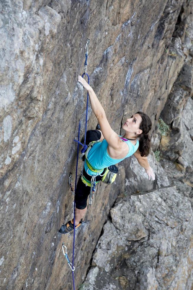 weibliche Klettererin, die über dem Abgrund hängt foto