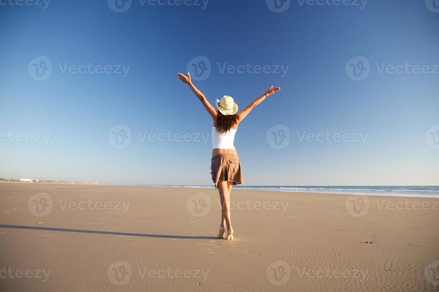 glückliche Frau mit Hut, der am Strand geht foto