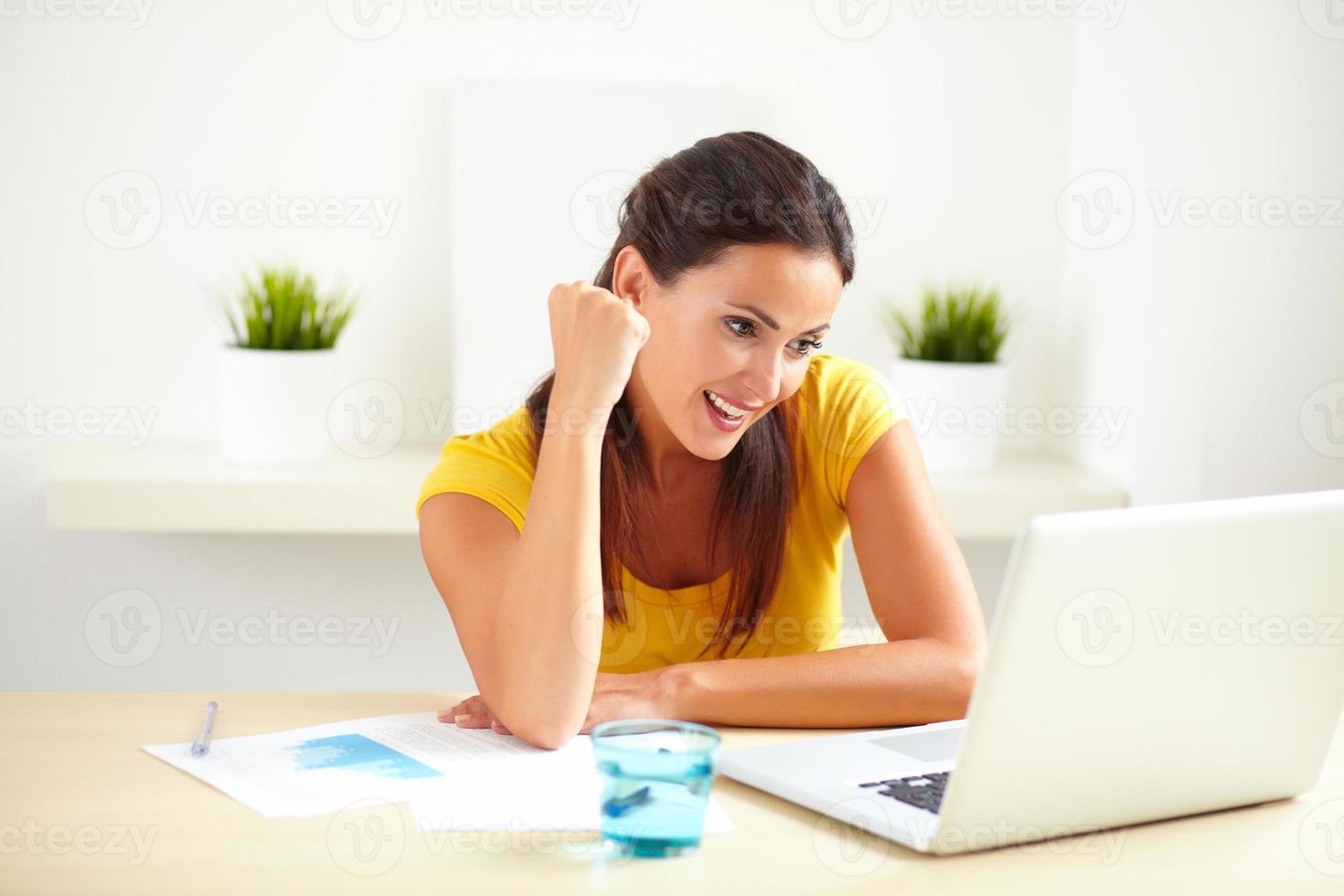 hispanische Mitarbeiterin, die in ihrem Büro feiert foto