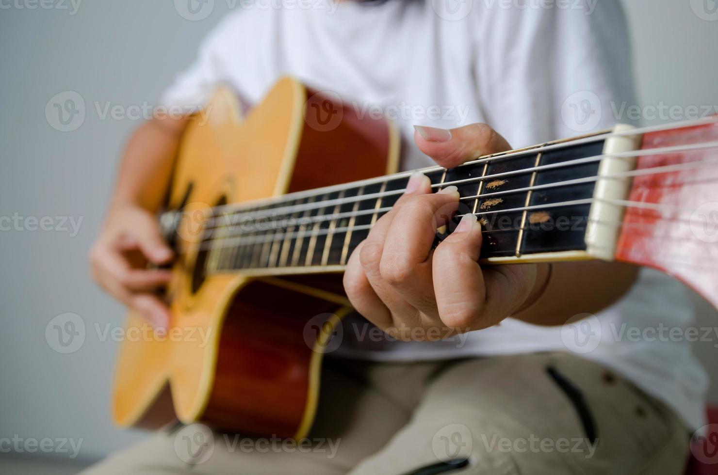weibliche Hand, die Musik durch akustische Gitarre spielt foto