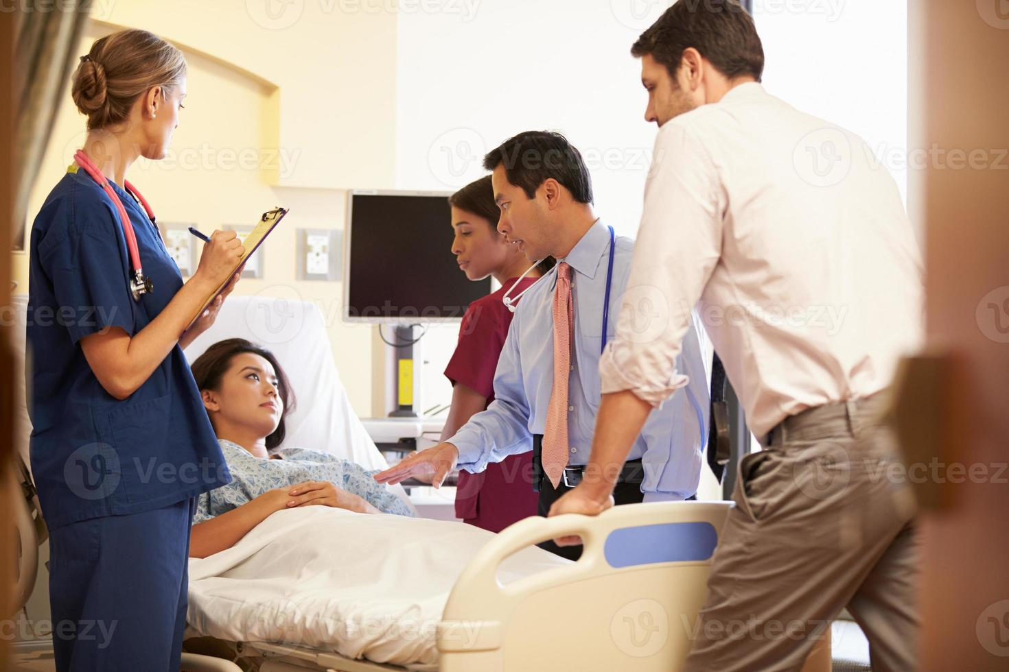 Mediziner neigen zu einer Patientin im Krankenhaus foto