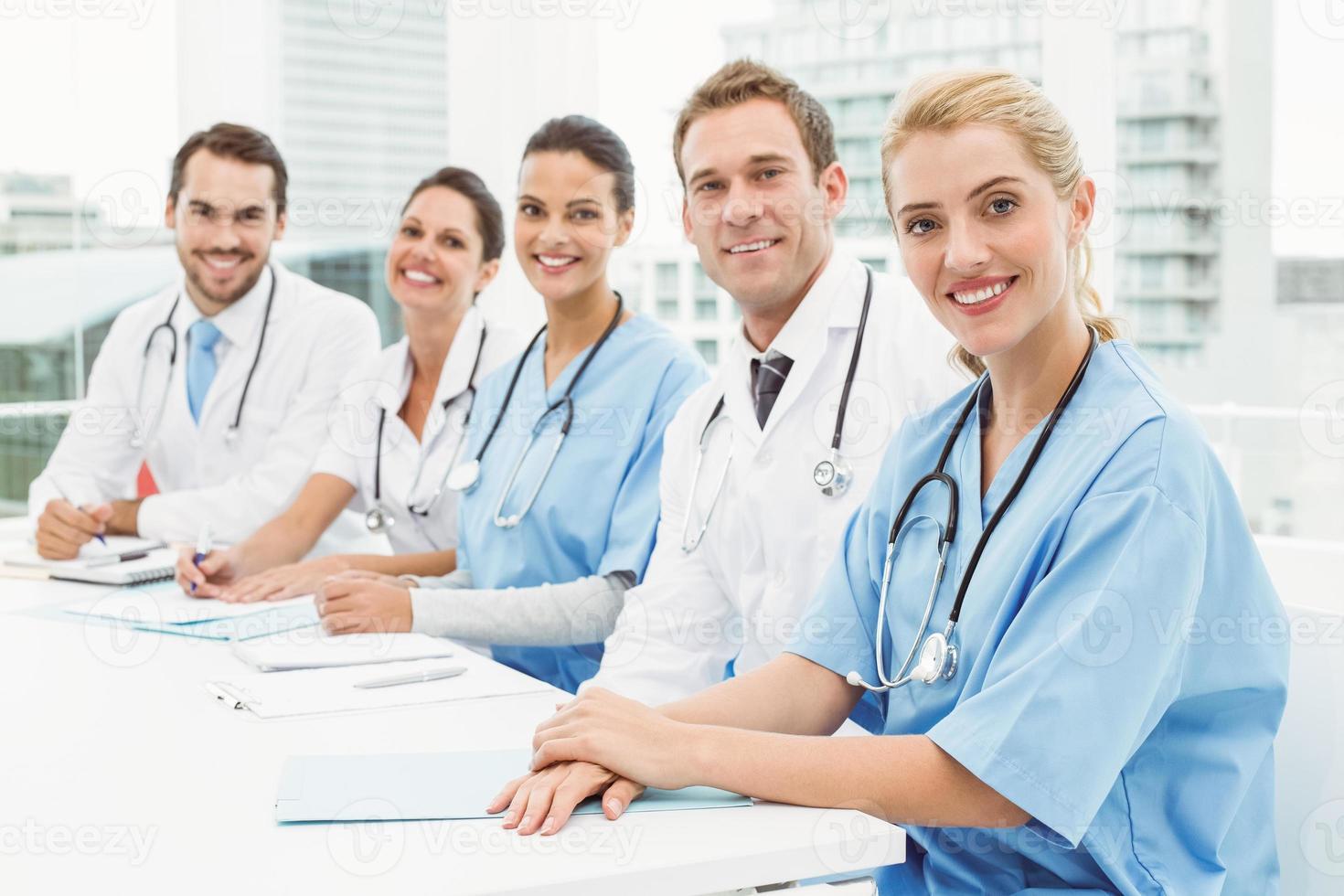 männliche und weibliche Ärzte sitzen in Reihe foto