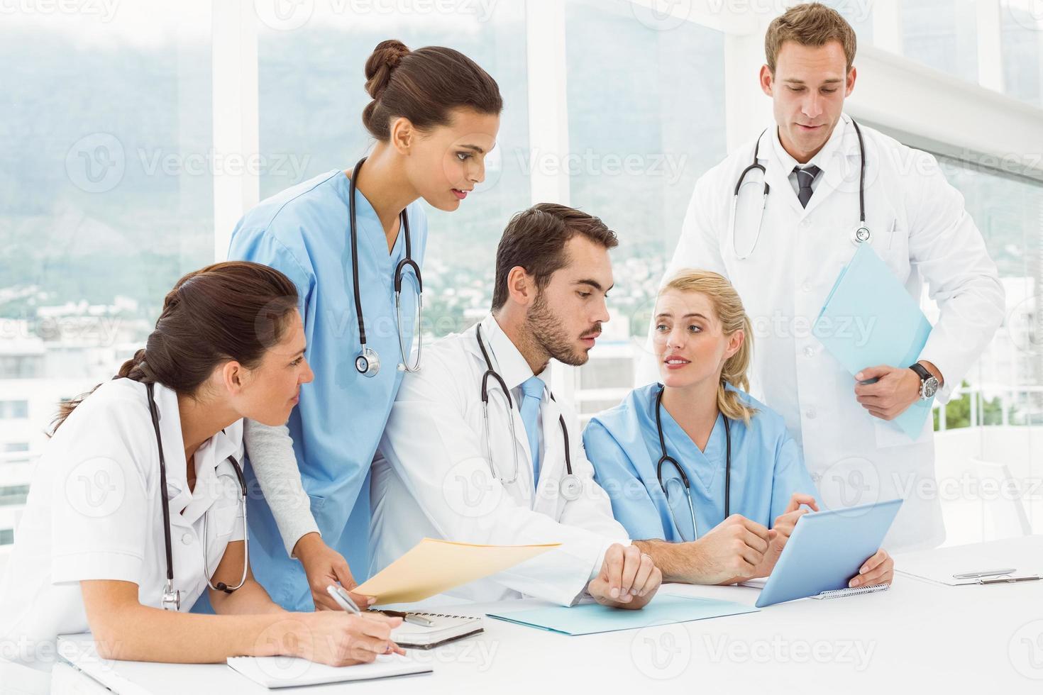 männliche und weibliche Ärzte mit digitalem Tablet foto
