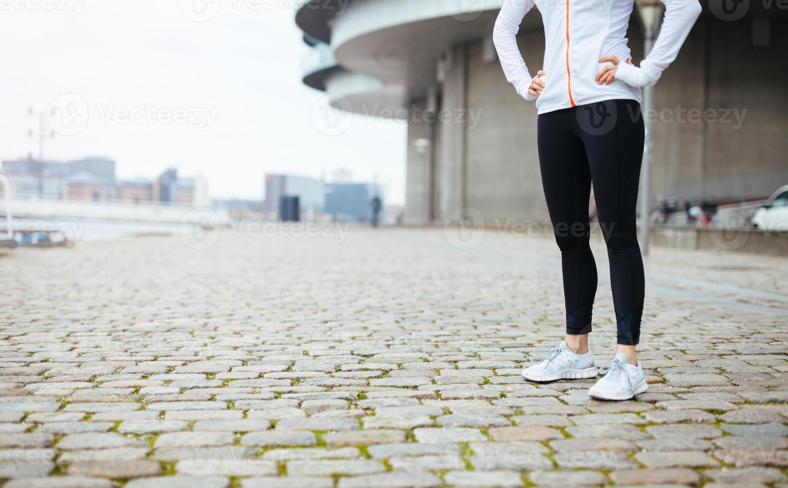Fitness-Frau, die auf Bürgersteig in der Stadt steht foto