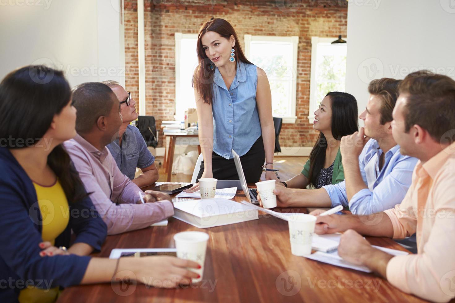 Chefin spricht Büroangestellte beim Treffen an foto