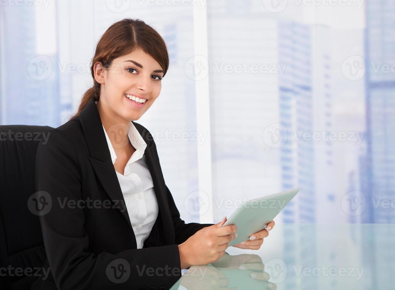 selbstbewusste Geschäftsfrau, die digitales Tablett am Schreibtisch hält foto