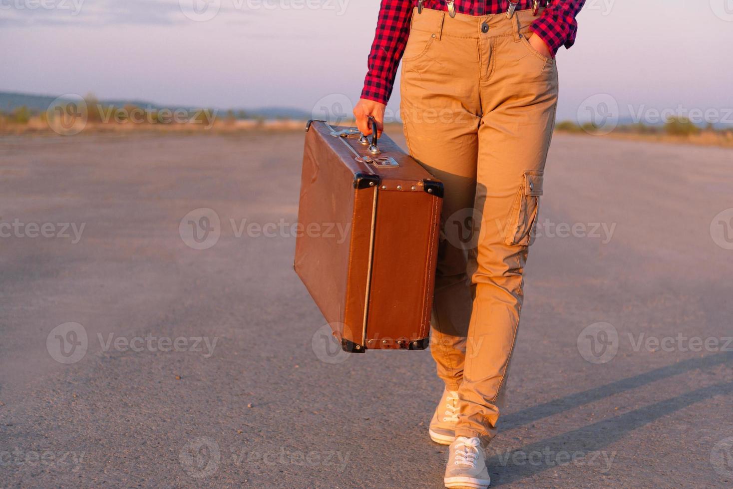Reisender geht mit einem Koffer foto