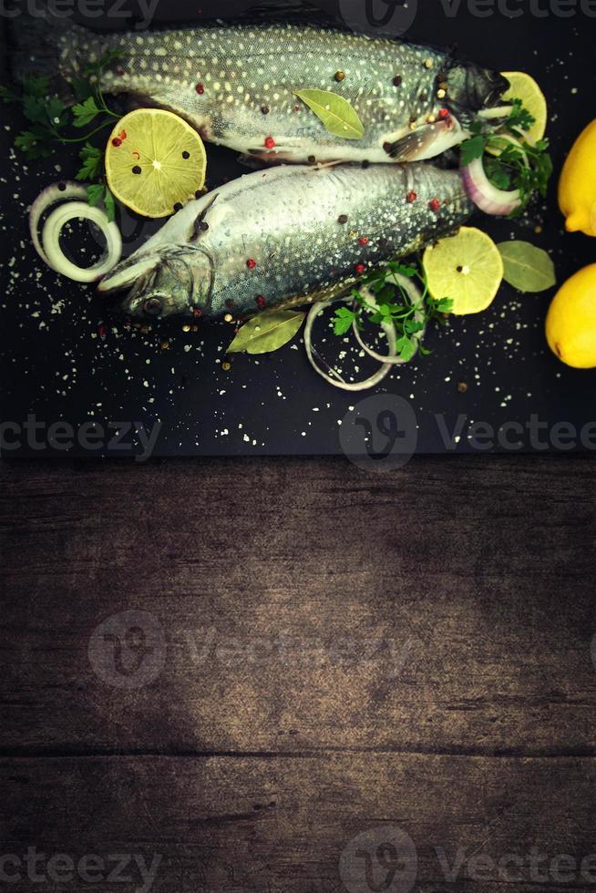 köstliche frische Forellen auf dunklem Weinlesehintergrund. foto