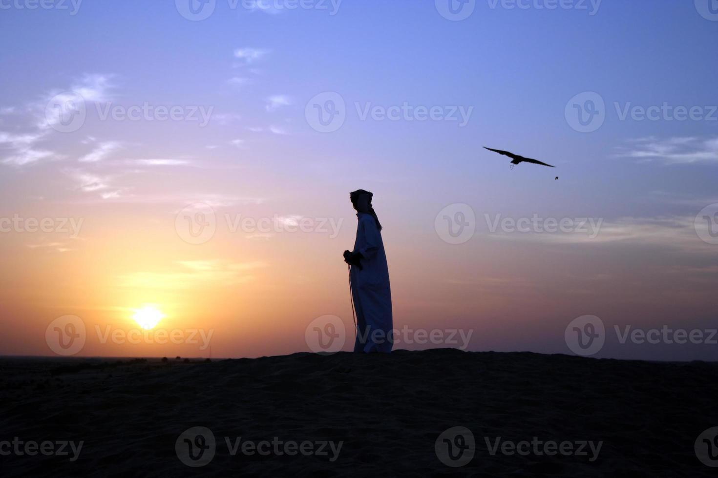 Silhouetten eines arabischen Mannes und eines Vogels bei Sonnenuntergang foto