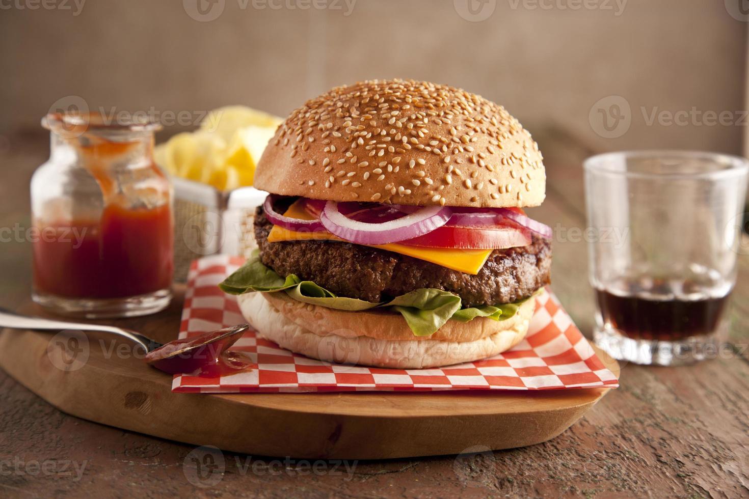 klassischer Cheeseburger mit Zwiebeln, Tomaten und Gurken Sesambrötchen. foto