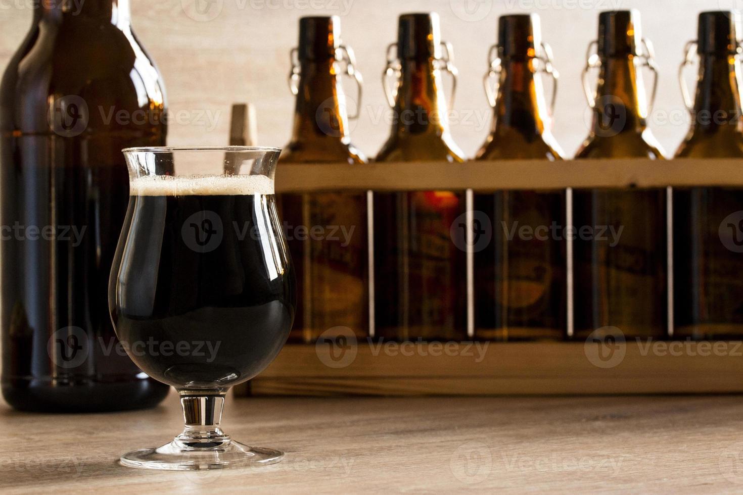 Glas braunes Bier, auf dem Tisch foto