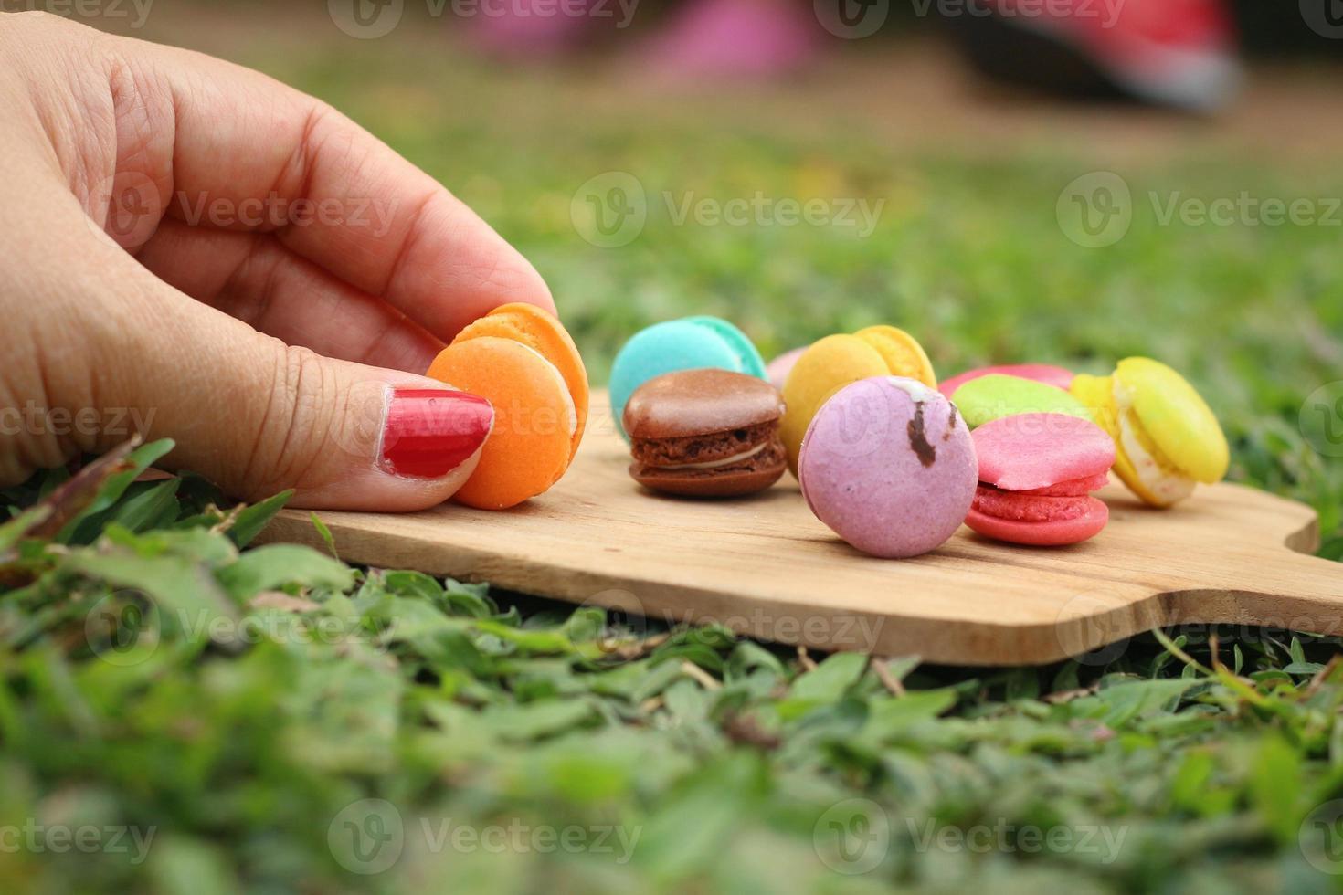 Hand wurden bunt von Macaron auf einem braunen Tablett gepflückt foto