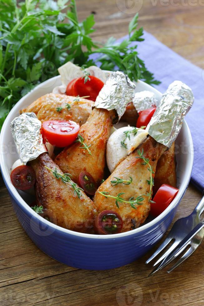 gebratene Hähnchenschenkel mit Kräutern und Gewürzen, Gemüse zum Garnieren foto
