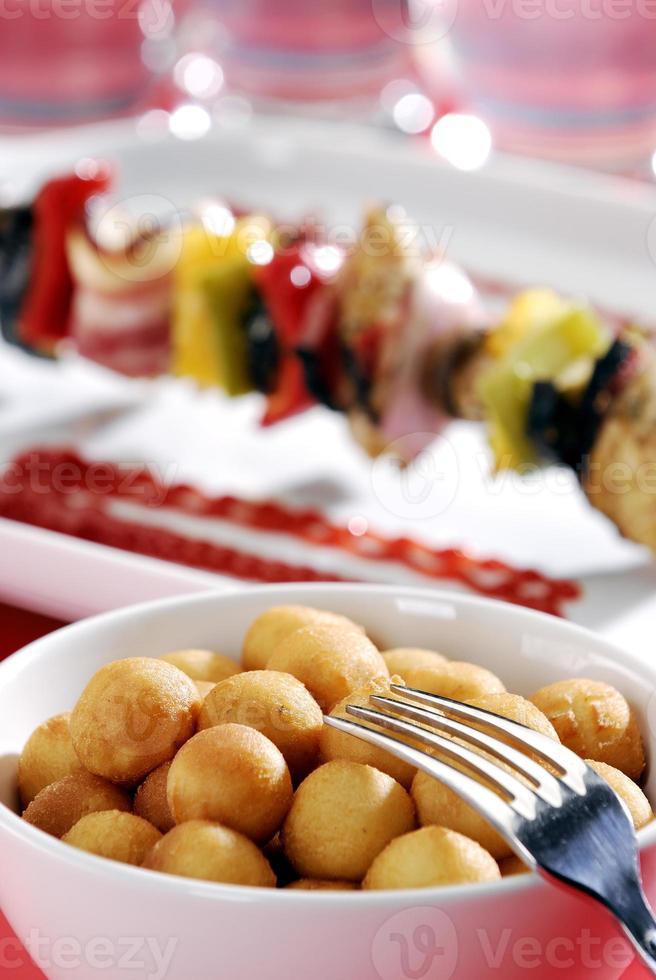 gebratene Kartoffelbällchen und Schaschlik im Hintergrund. foto
