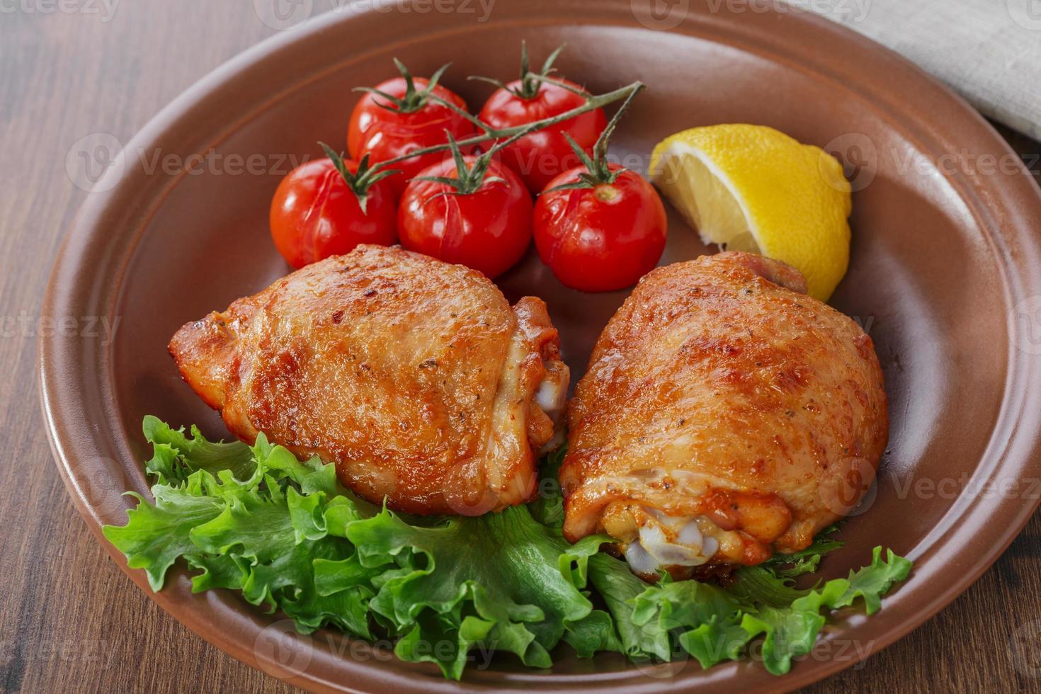 gebackener Hähnchenschenkel mit Kirschtomaten und Zitrone foto