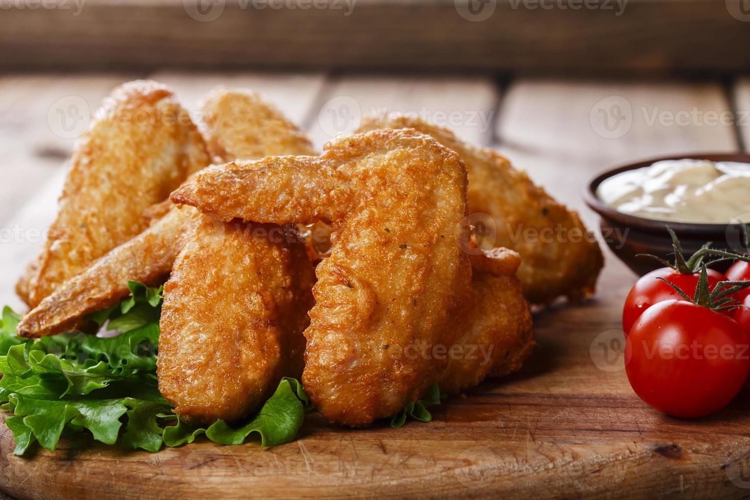 gebratene Hühnerflügel mit Sauce und Tomaten foto