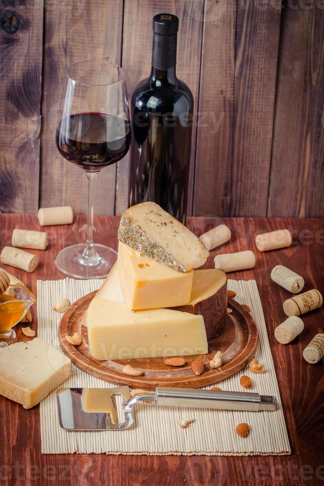 verschiedene Käseteller mit Rotwein, Nüssen und Honig foto