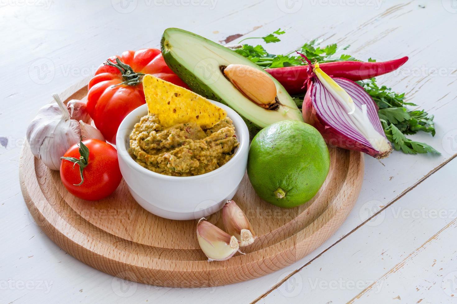 Guacamole und Zutaten - Avocado, Tomaten, Zwiebeln, Knoblauch, Limette foto