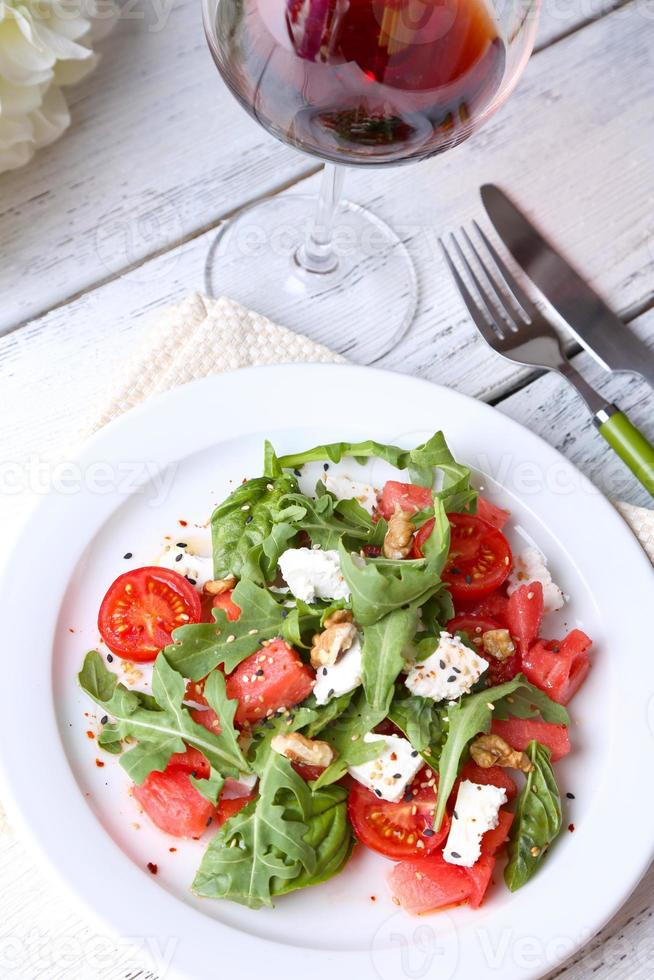 Salat mit Wassermelone, Feta und Basilikumblättern auf Teller foto