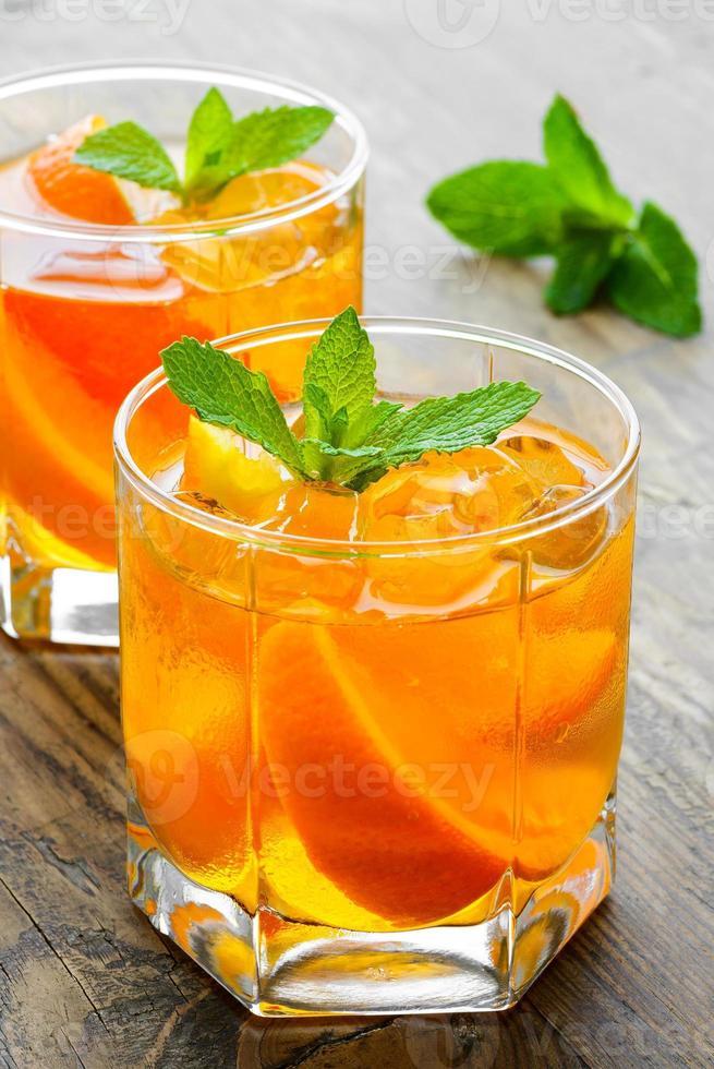 kalte Getränke mit Eis und Minze. Orangencocktail auf rustikal foto