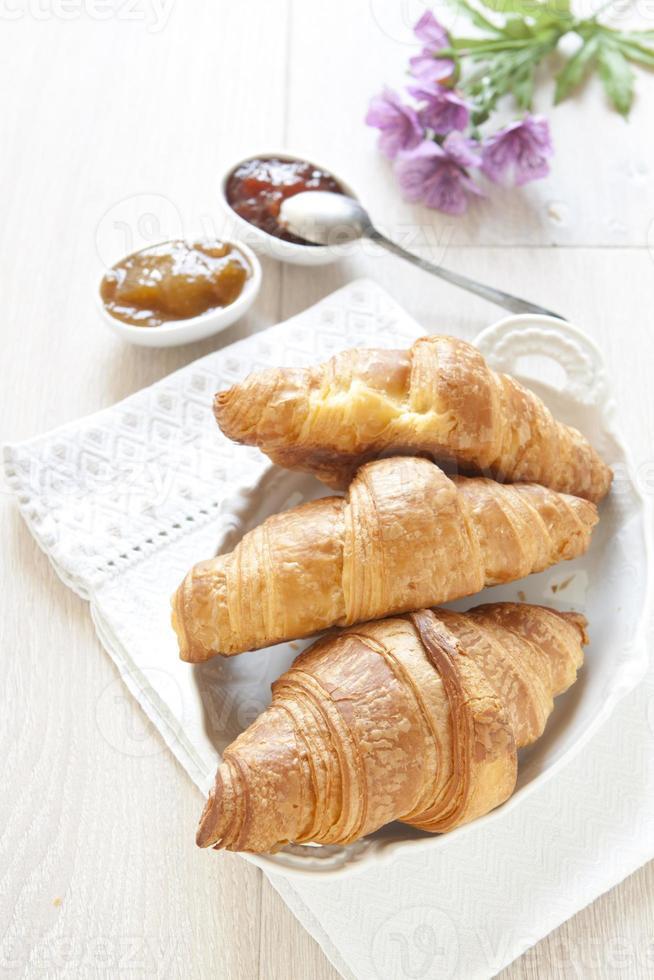 Croissants auf dem Tisch mit Marmelade foto