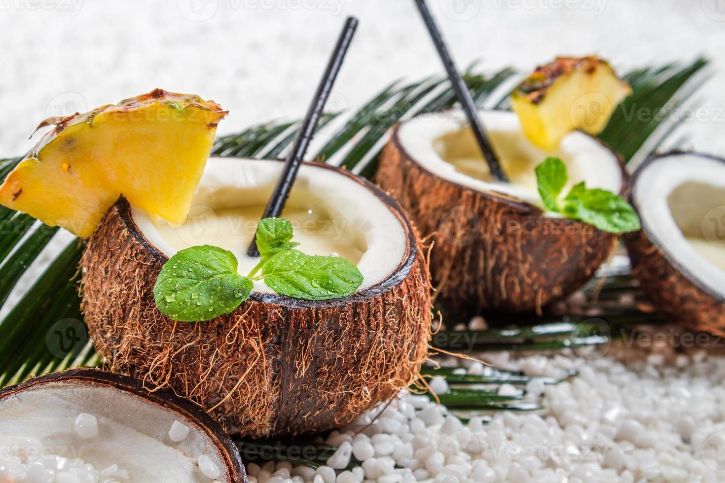 Nahaufnahme von Pinacolada mit Minzblatt in der Kokosnuss foto