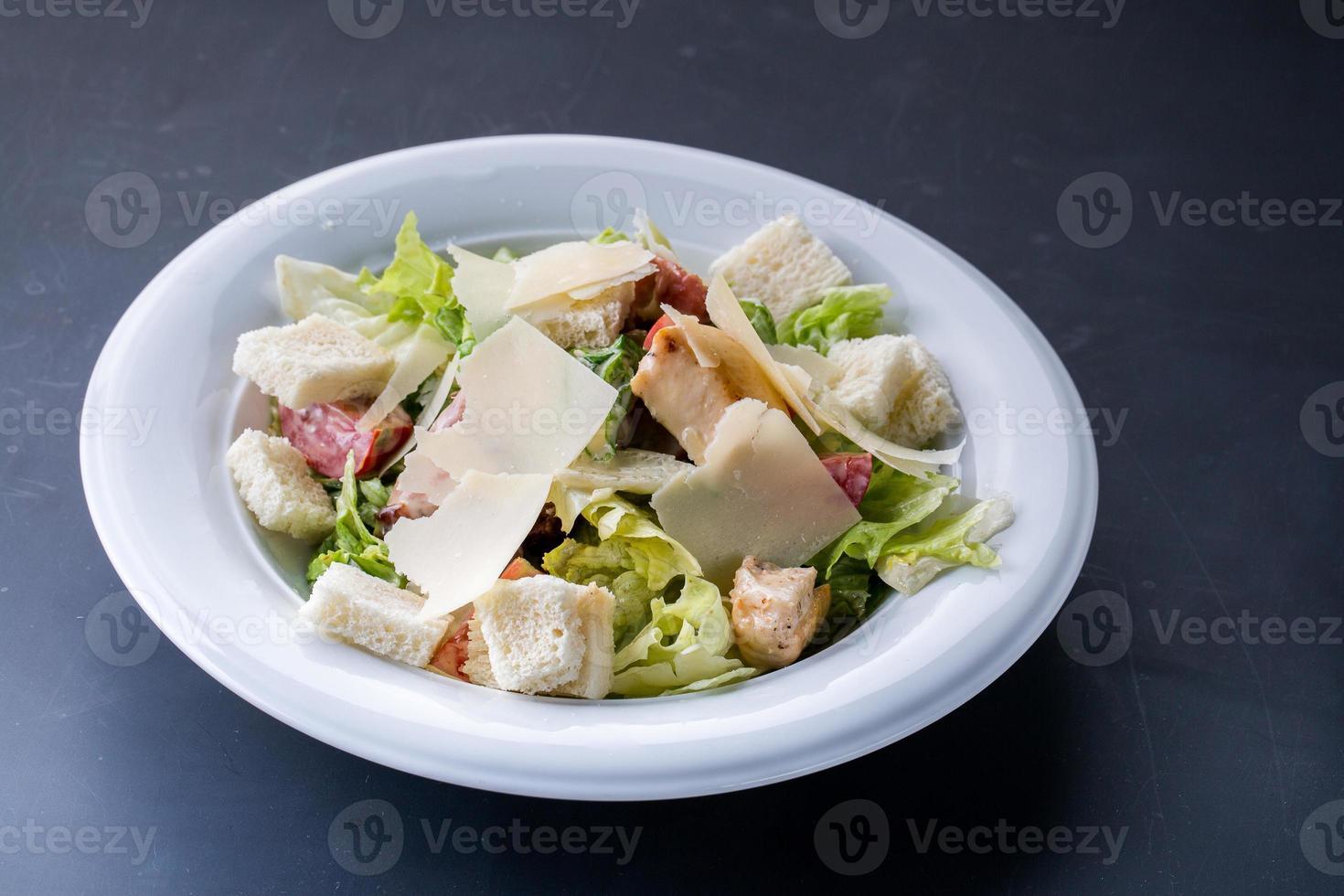 gesunder gegrillter Hühnchen-Caesar-Salat mit Käse und Croutons foto