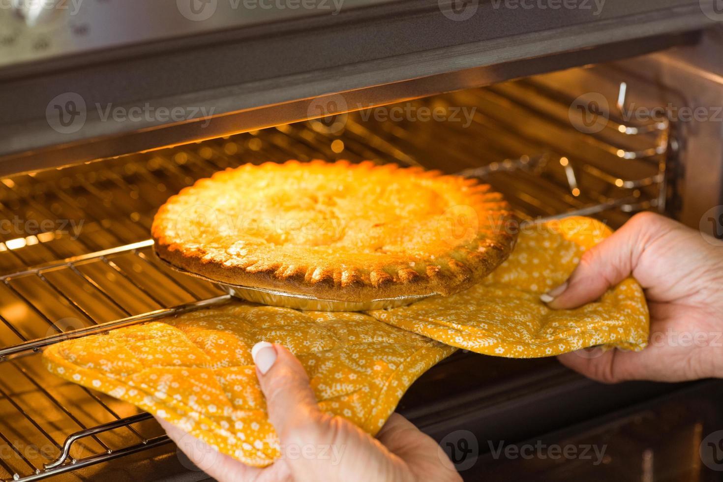 Frau, die frischen Kuchen aus dem Ofen nimmt foto