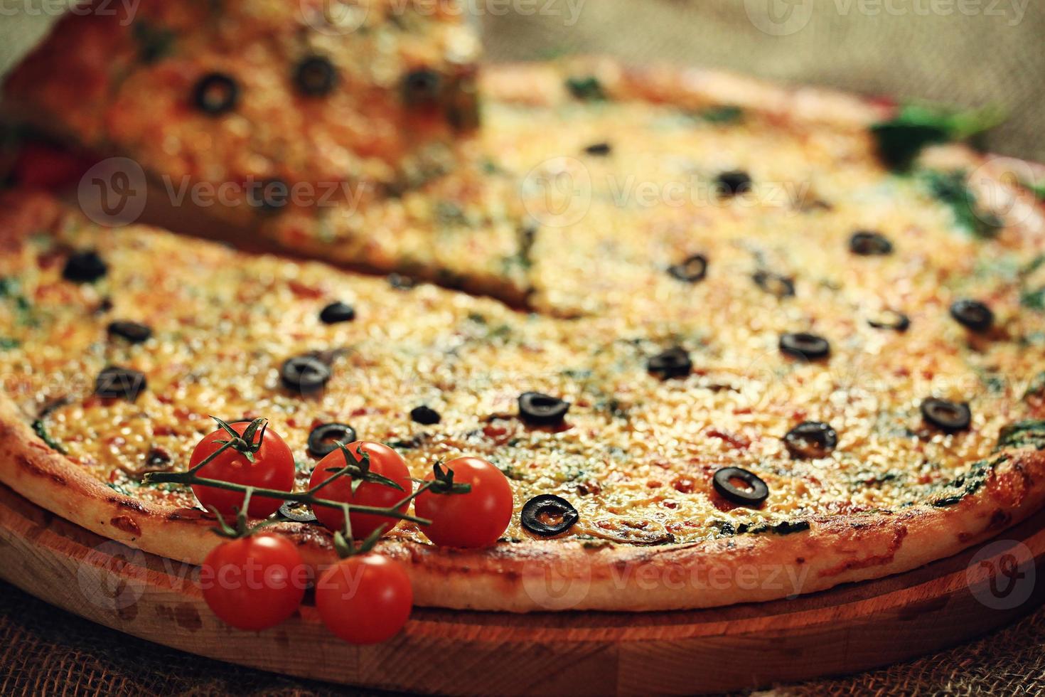 Pizza mit einem Stück geschnitten, leckeres Gebäck foto