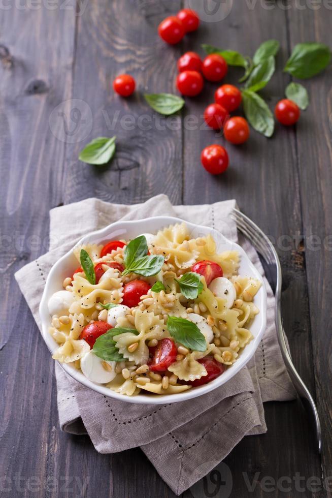 Nudelsalat mit Tomaten, Mozzarella, Pinienkernen und Basilikum foto