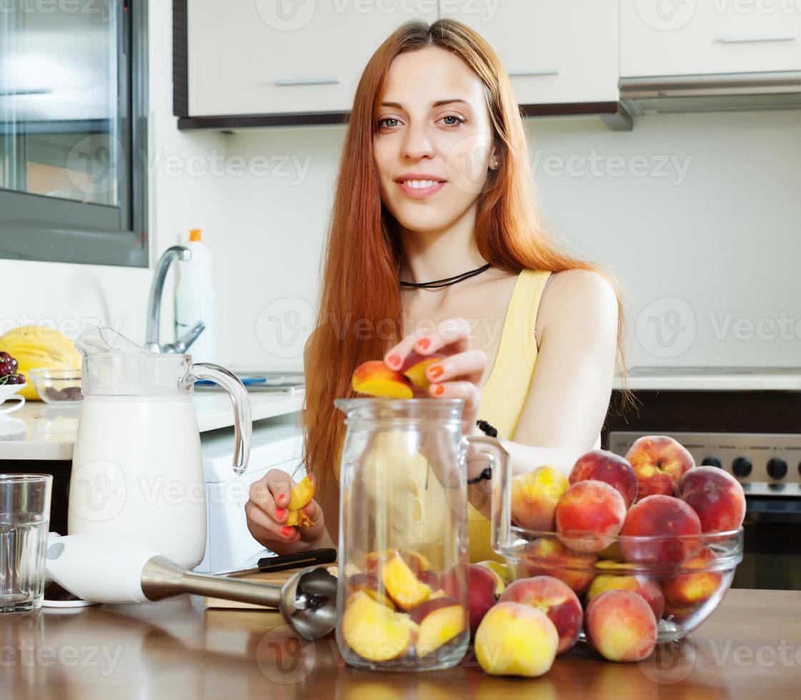 positives Mädchen, das Getränke von Pfirsichen kocht foto