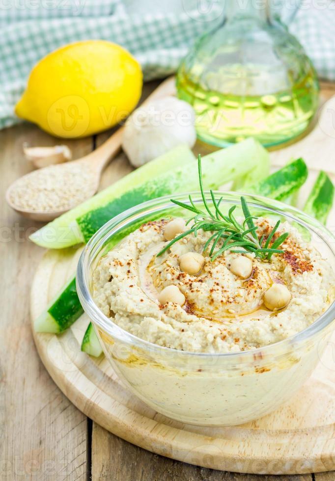 Schüssel mit klassischem Hummus, bestreut mit Paprika und Sesam foto