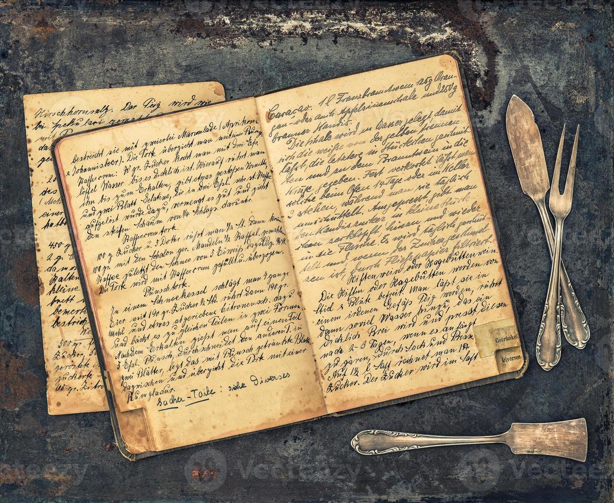antikes Besteck und handgeschriebenes Vintage-Rezeptbuch foto