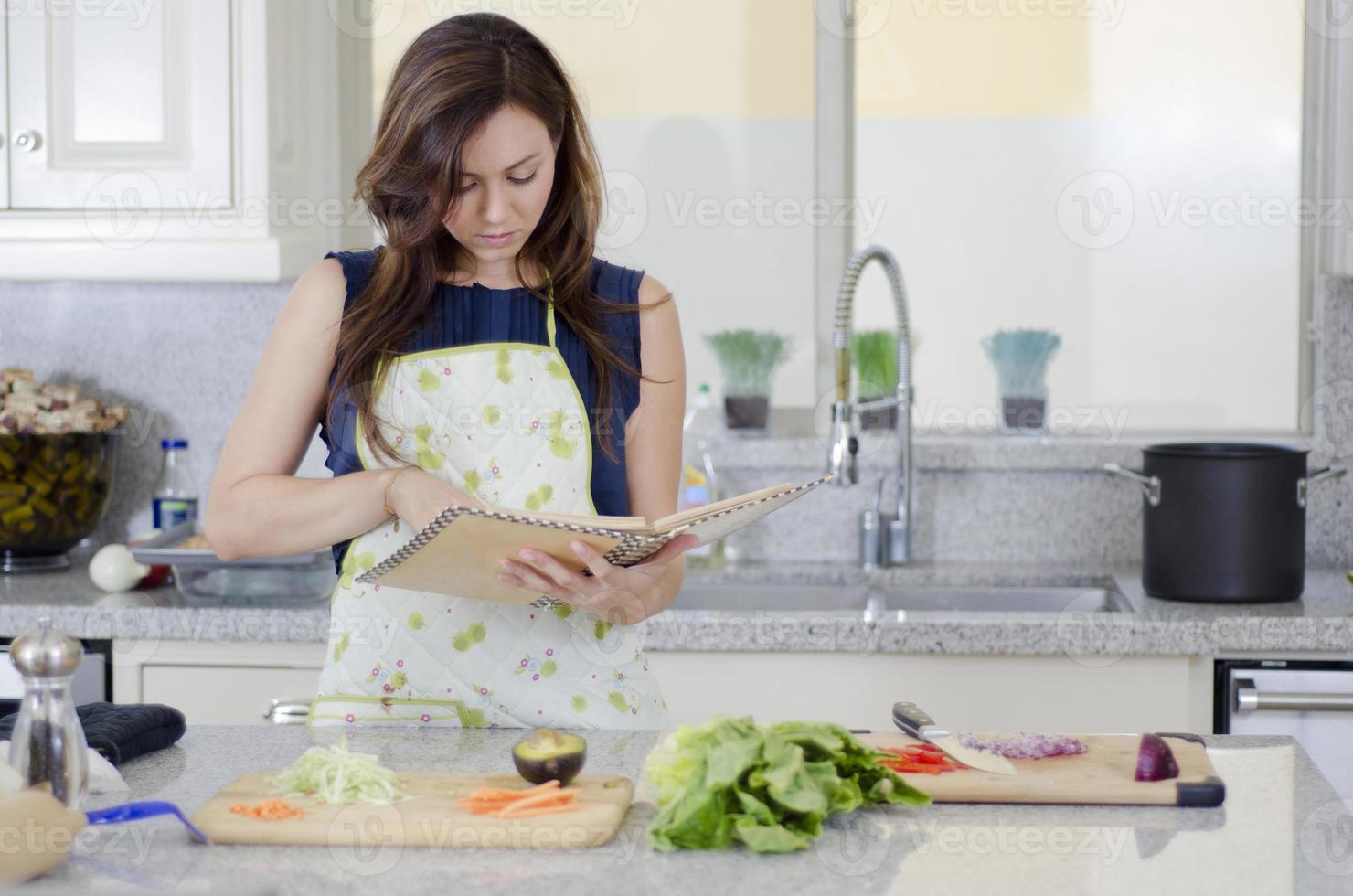 schöne Hausfrau, die ein Rezept kocht foto