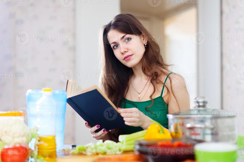schöne Frau liest Kochbuch für Rezept foto