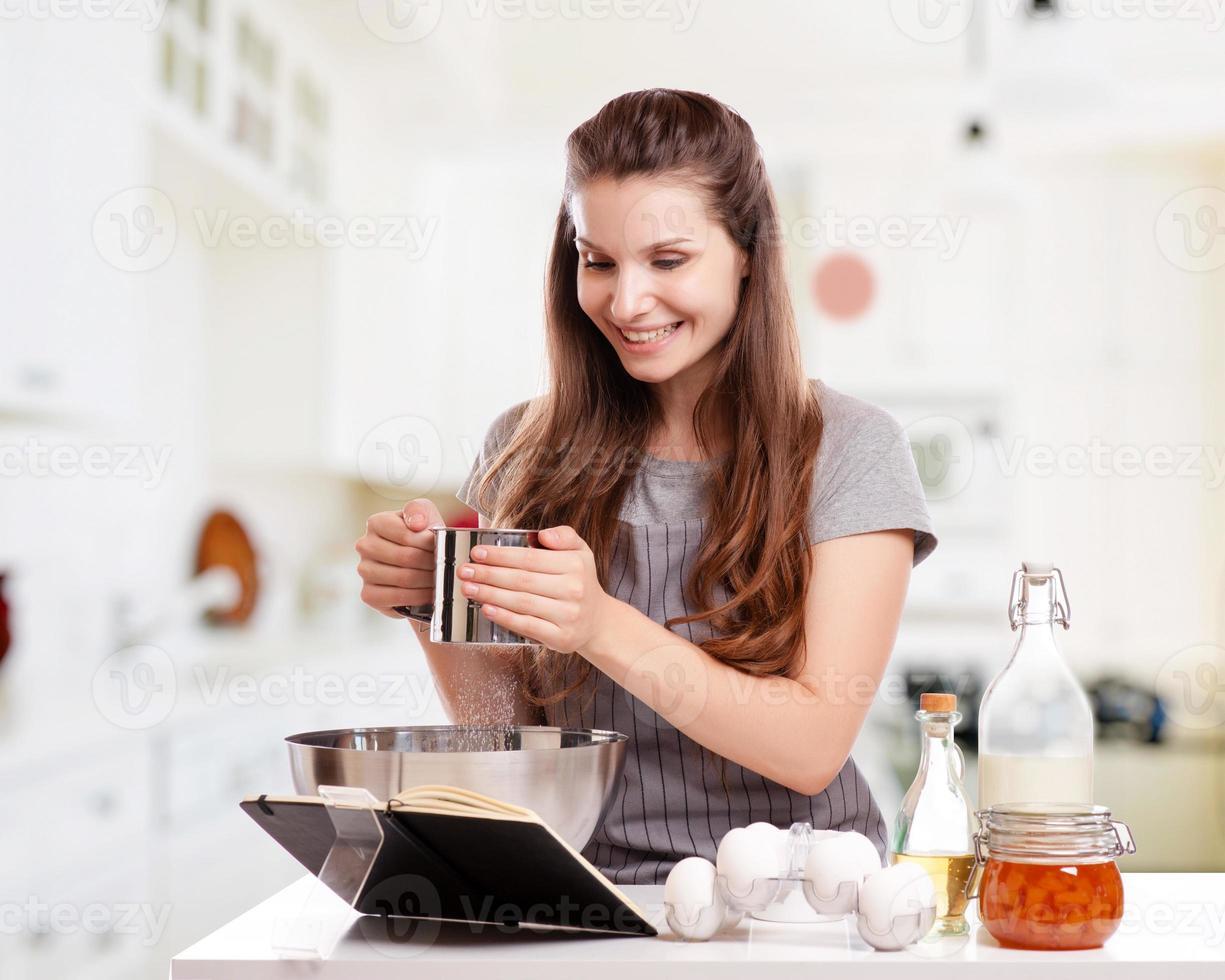 Frau backt zu Hause nach Rezept foto